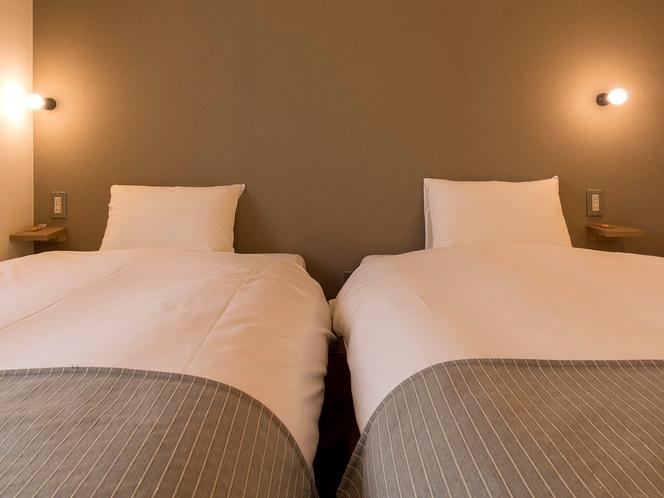 【エコノミーツインルーム】枕元にはスマホの充電に便利なコンセントと棚があります