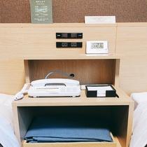 ツインルームのベッド横の棚です。時計はアラーム機能もご利用頂けます。