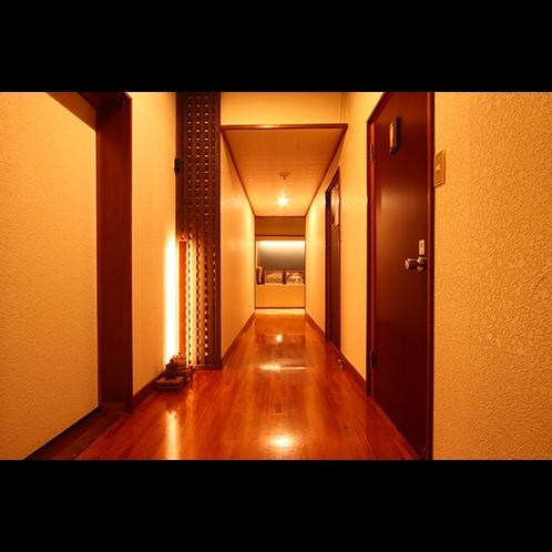 一階の廊下。フロントからお風呂にむかう導線の空間。正面には、モノクロの古き福岡旅館の写真も。