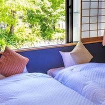 【倶楽部ルーム】和室にローベッドを2台配した空間。畳の心地良さとベッドの快適さで、のんびり寛ぐ