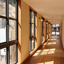 *【宿泊棟館内】大きな窓から明るい光が差し込む廊下。