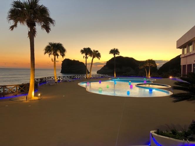 夕暮れの風景、金色の空とライトアップされたプール