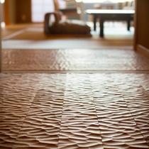 客室玄関の床板は伝統技法のなぐり加工で化粧し、凹凸のある木肌の感触が足裏に心地よく伝わります