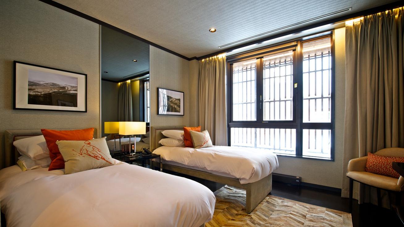 *[2階ベッドルーム]シングルベッドが2台置かれた、シックで優雅な約20m2の寝室。