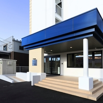 """新館アプローチ:青と白の建物が目印。""""お気軽に滞在できるホテル""""を目指して 車いす対応スロープも完備"""