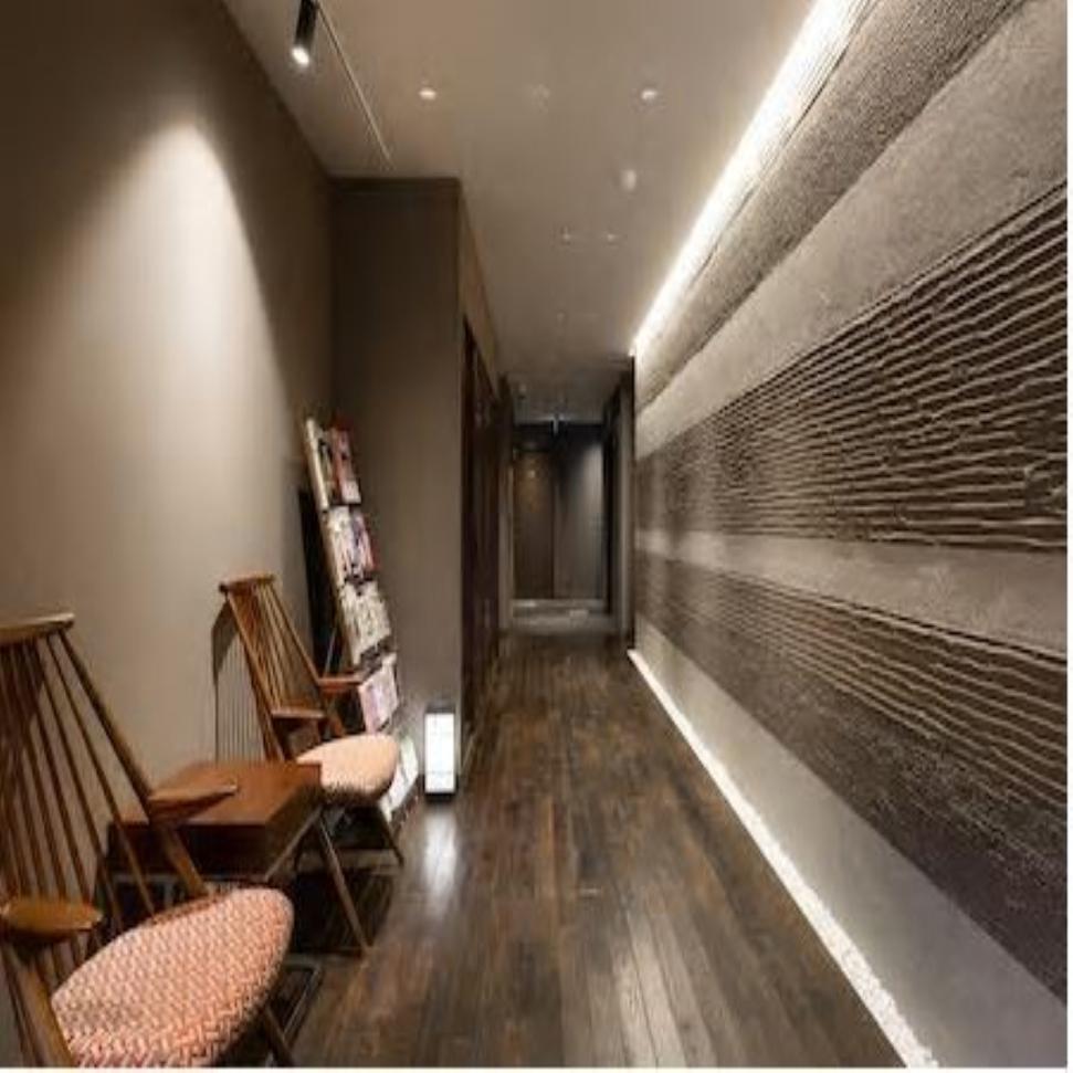 【ロビー空間】機能性、意匠性を兼備した壁面の漆喰デザインに柏木工製シビルチェアが調和し壮観なロビー。
