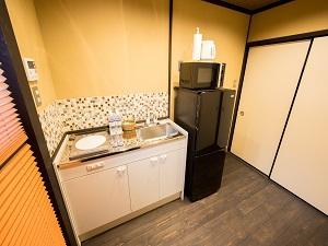 冷蔵庫や電子レンジ、ポットなどがそろったキッチン。