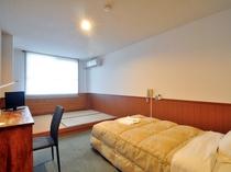【和洋室シングル】シングルタイプのベッド一台と、畳に2組の布団を引くことで最大3名まで収容可能です。