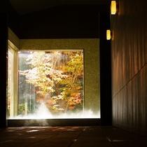 日帰り温泉(ご宿泊者様無料)/紅葉の八風温泉/扉の先には、開放的なガラス窓越しに映える鮮やかな紅葉