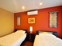 【フロント側1F・ツインルーム】赤の壁が印象的な南国らしい寝室になっております。