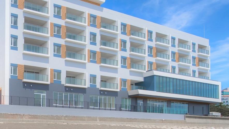 【外観】白を基調とした海と空の青に生えるリゾートホテル