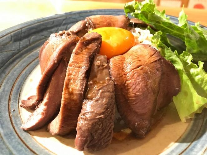 鹿肉月見丼。やわらかく調理した味付けモモ肉と旨味ダレ。卵黄を絡めて、かまど炊きごはんをかきこむ!