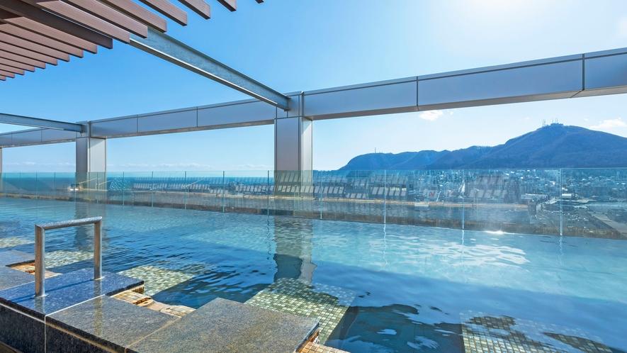 【大浴場】天空露天風呂からは函館山を一望。昼は明るい日差しが差し、夜は幻想的な雰囲気に…。