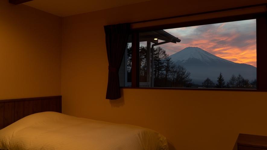 和モダンルーム―額縁のような大きな窓から見える夕焼けの富士山