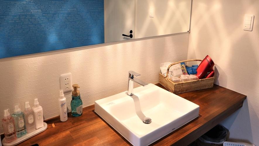 【客室洗面】スッキリしたマリンカラーの洗面台。シャワールームは、レインシャワー対応。