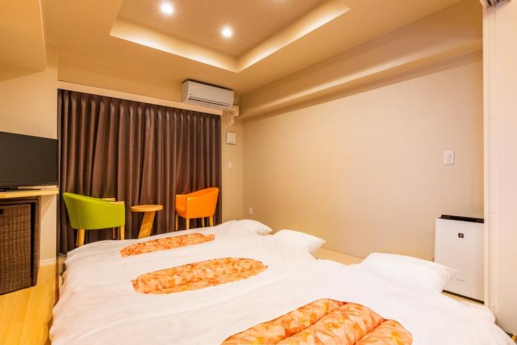 和洋室。定員5名様です。ベッドが2台。3~5名様はこちらにお布団を敷いて頂きおやすみください。