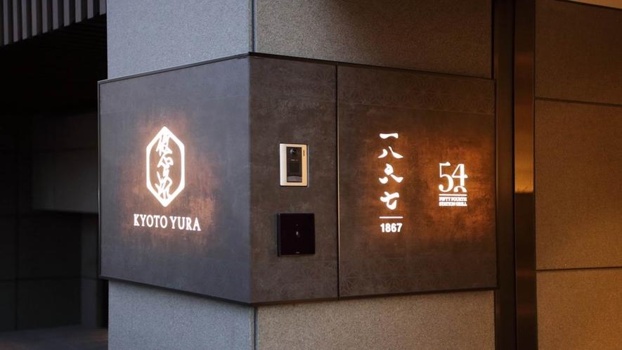 """【入口サイン】鴨川の流れをイメージした""""悠洛'のロゴサイン。入口は三条通沿いに面しています。"""