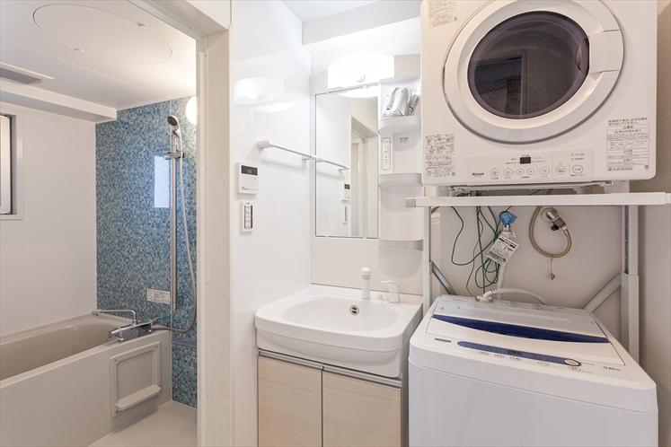 【洗面台まわり】大きく明るい洗面台の横には洗濯機(洗剤あり)とガス乾燥機を完備
