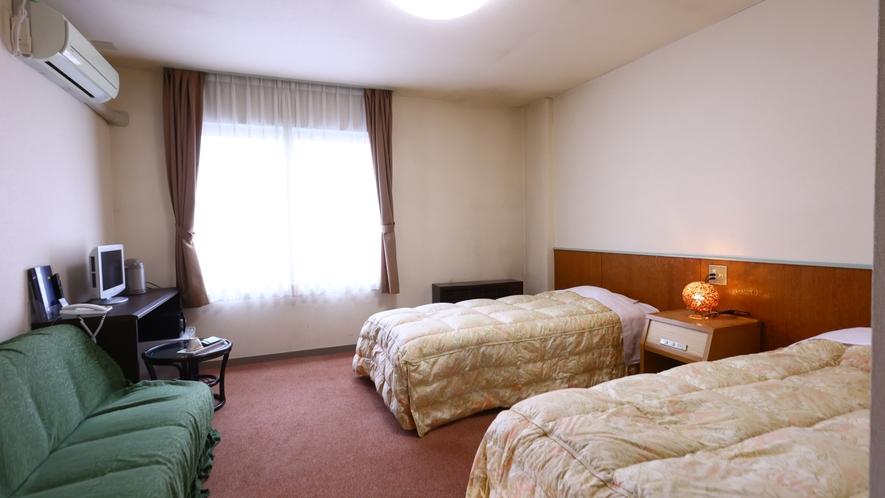 洋室ツインルーム一例。冷暖房完備。ごゆっくりお寛ぎください。