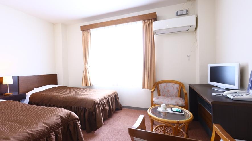 洋室ツインルーム一例。茶色を基調としたシックなお部屋。