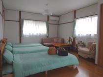 洋室Aは明るく広々とした4ベッドのお部屋。木製パレットを使ってホストがDIYで作ったテーブルや、ベッ