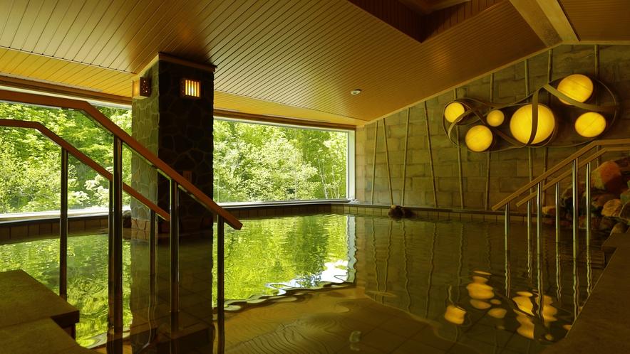 内風呂【大浴場】「山月の湯」内湯…湯量豊富な自家源泉かけ流しの湯を、大自然を望む湯舟でご堪能下さい。
