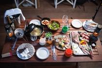 鮮やかなオードブルやオーブン料理のあとは、豪快な肉料理がキャンプ気分を盛り上げます(イメージ)