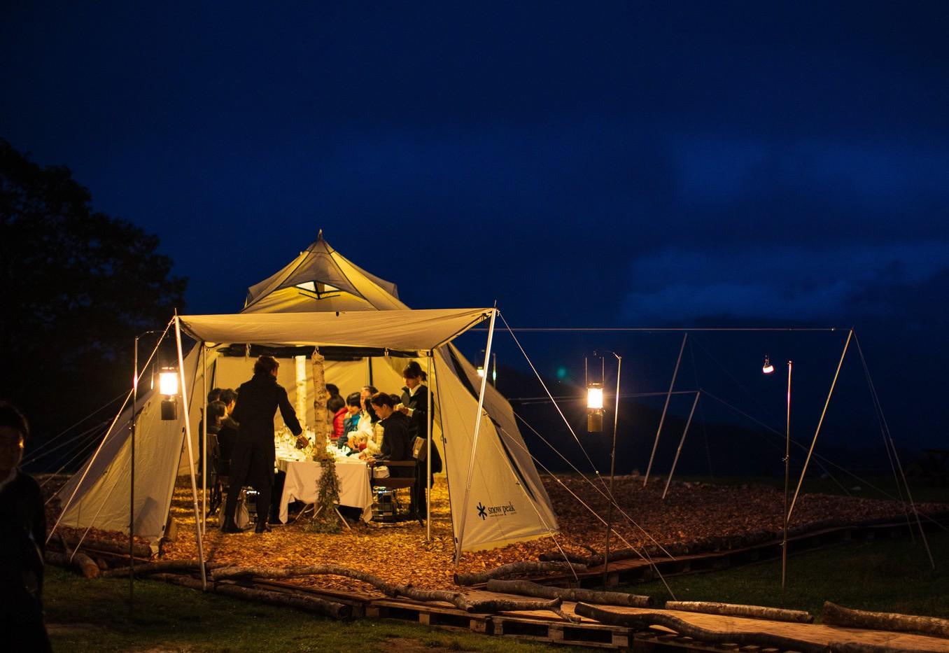 真っ暗なフィールドに作られるダイニングテントの中でコースディナーをお楽しみいただけます