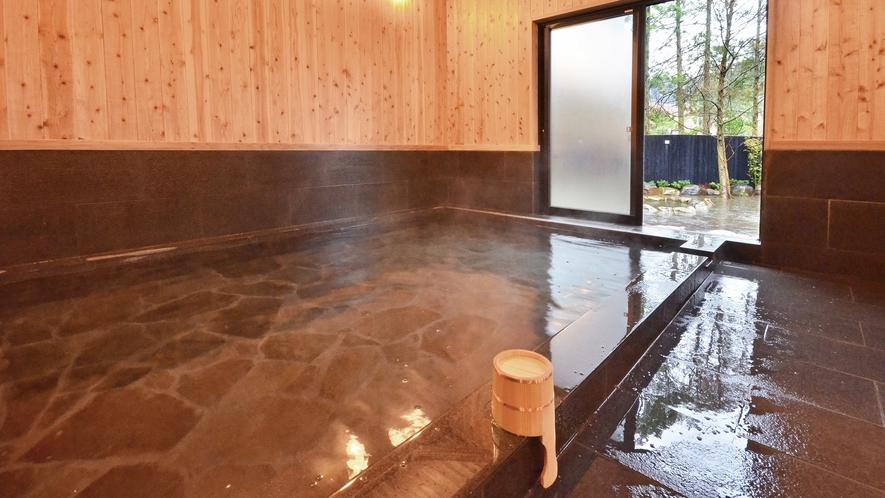 大浴場「遊湯館」_内湯_檜の壁に赤御影の浴槽が落ち着いた雰囲気を醸し出します。