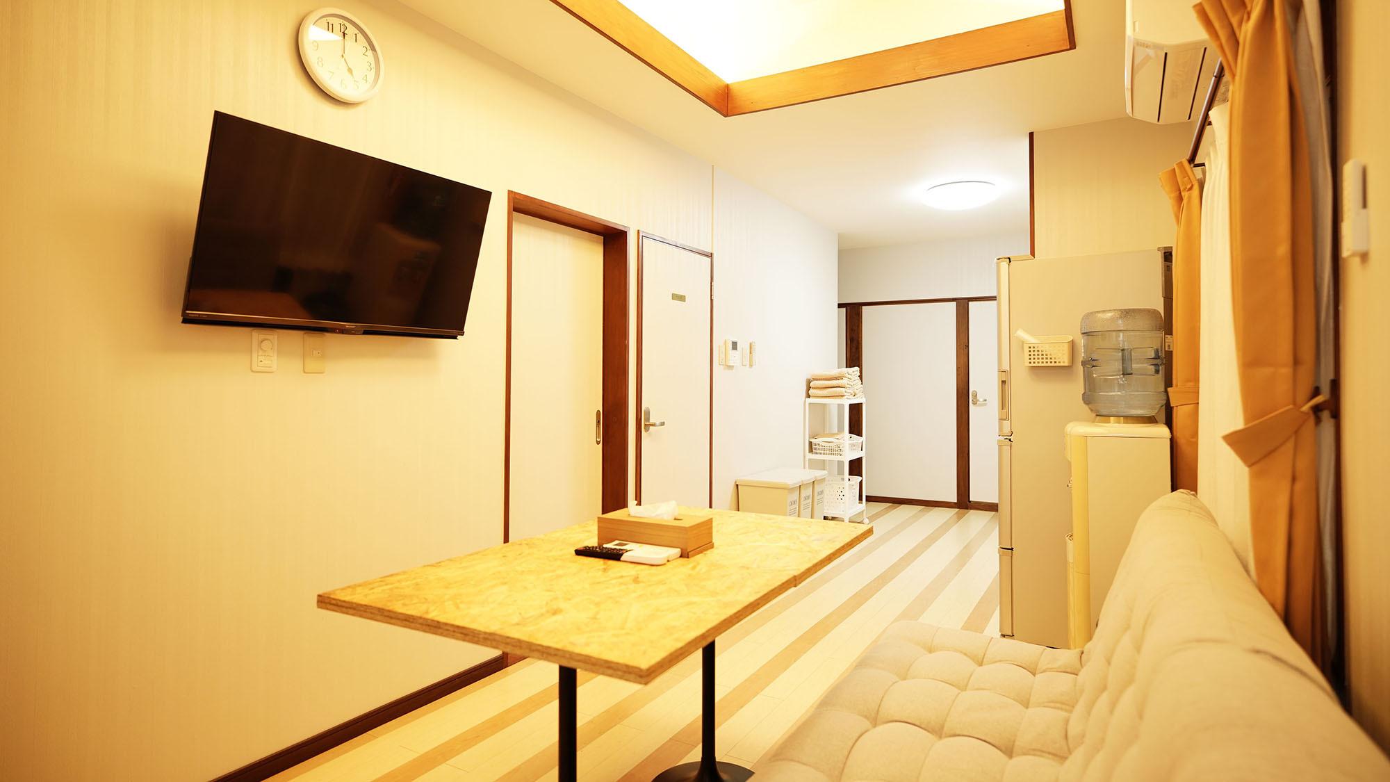 ・201号室:明るい照明で温かみのあるリビングルーム