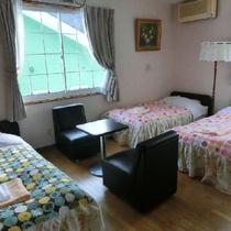 明るい花柄のベッドカバーがかわいいペンションのお部屋。