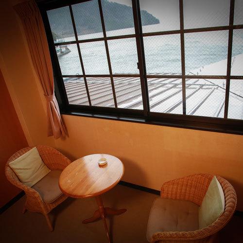 洋室の窓辺には椅子とテーブルがあります