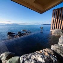【天海の湯】湯が奥の海に向かって落ち、海と一体となった幻想的なお風呂です。