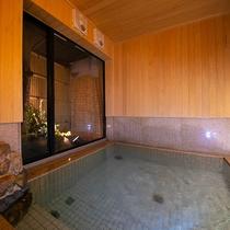 木のぬくもりを感じる浴室の壁は檜で出来ており、小さな坪庭には目でも楽しんでいただけるよう季節のお花を