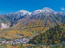 秋の奥飛騨温泉郷・平湯峠。冠雪の山頂と紅葉のコントラストが美しい