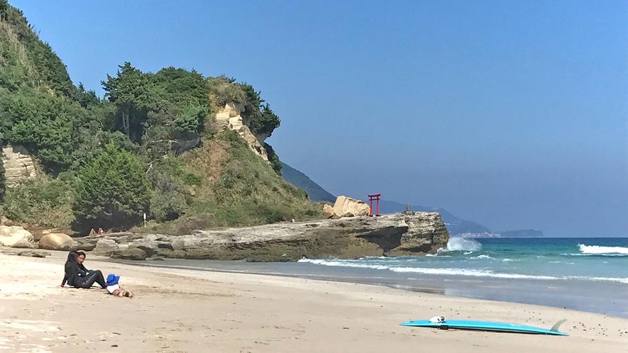浜に建つ鳥居とサーファー
