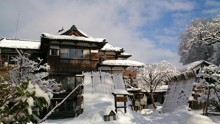 【冬の外観】すっぽりと雪に覆われた嵐渓荘。夜は温かな明かりが灯ります。