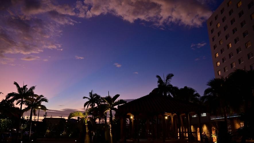 【ホテル外観】美しい空の色に映える南国植物のシルエット