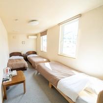 【本館洋室】3名様まで宿泊可能なお部屋。ベッドが3台並んでいます。