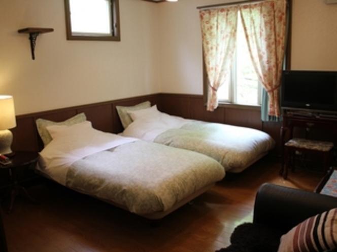 ベッドの間が付けられる落ち着いた雰囲気のツイン角部屋