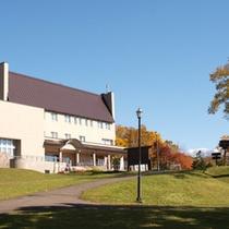 秋の紅葉とホテル外観