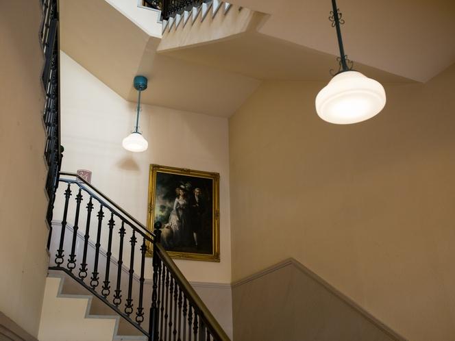 <ロビー>階段にもこだわりの絵画を展示しております。