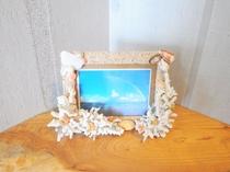 【洋室ツイン】貝殻で縁取られたフォトフレーム。中には綺麗な海の景色が飾られています。