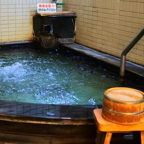 天然温泉掛け流しの大浴場(男性)黒を基調とした落ち着いた雰囲気。