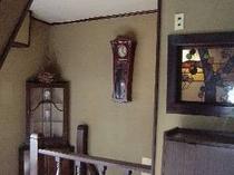 アンティークな時計とステンドグラスが並ぶ階段