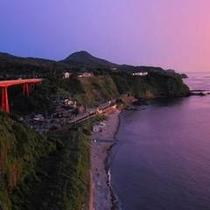 沈む夕日に染まる橋と駅