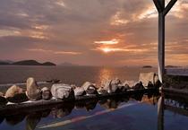 【大浴場展望露天風呂】湯けむりの向こうに見える美しい夕日と瀬戸の島々、遠くに行きかう船。