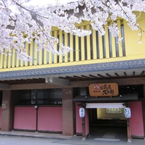 【玄関】春は満開の桜でお出迎え。自然に囲まれた渓流沿いの静かで落ち着いた環境にある温泉宿です。