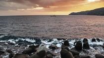 【周辺景観】夕焼けの海岸で漁船を見送る