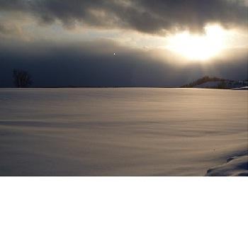 【冬】雪原の中に薄っすらと浮かぶ夕陽